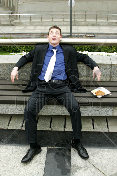 a man resting on a bench with his lunch by the side stock photo