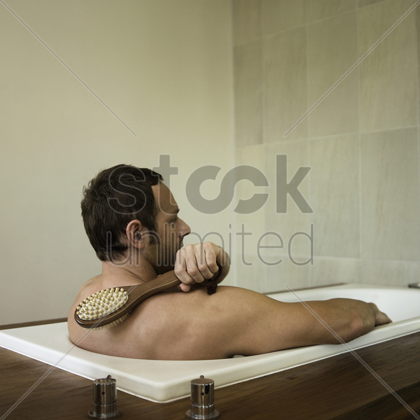 a man scrubbing his back in the bathtub stock photo