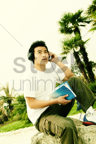 a man sitting on the lakeside listening to music on his headphone while reading a book stock photo