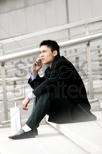 a man sitting on the stairs talking on the hand phone stock photo