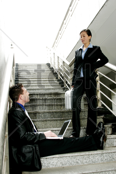 a man sitting on the stairs using his laptop while talking to a woman stock photo