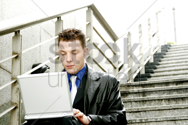 a man sitting on the stairs using his laptop stock photo