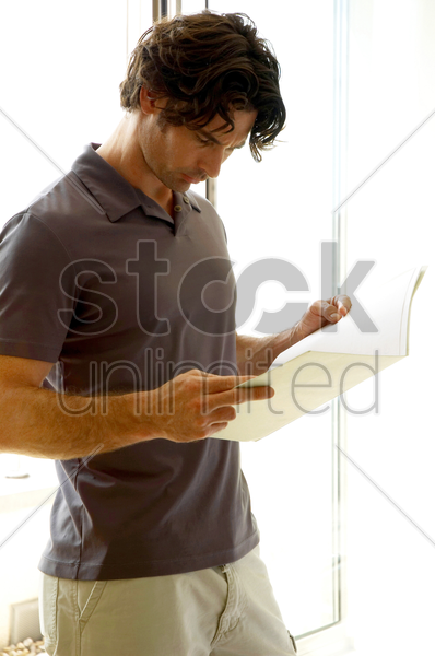 a man standing by the window reading documents stock photo