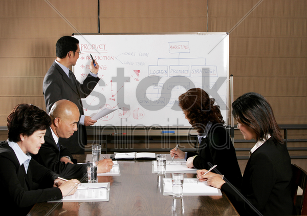 a man teaching while the others writing stock photo