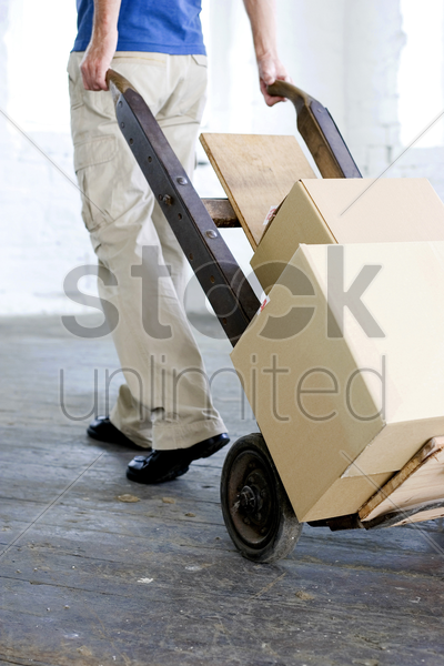 a man transferring goods using trolley stock photo