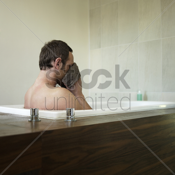 a man wiping his face with a face towel stock photo