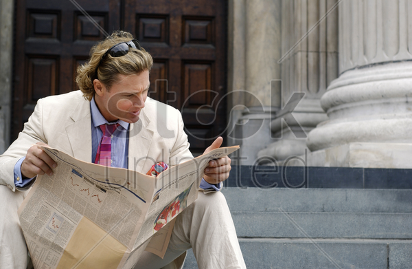 a man with a sunglass on his head sitting on the stairs reading newspaper stock photo