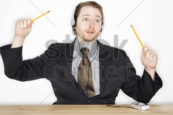 a man with headphone tapping along with pencils while listening to music connected from his hand phone stock photo