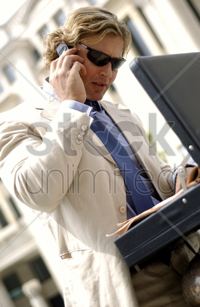 a man with sunglass searching for documents from his briefcase while talking on the hand phone stock photo