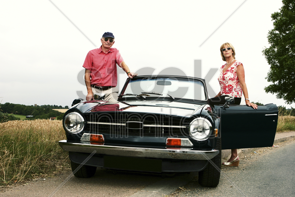 a married couple standing beside their roofless car stock photo