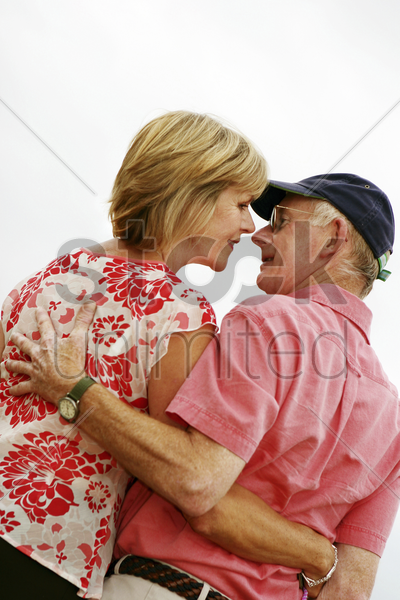 a married couple standing close to each other for a kiss stock photo