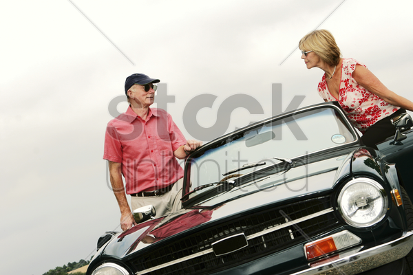 a married couple standing next to their roofless car talking stock photo