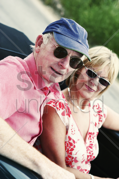 a married couple with sunglasses driving around in their roofless car stock photo