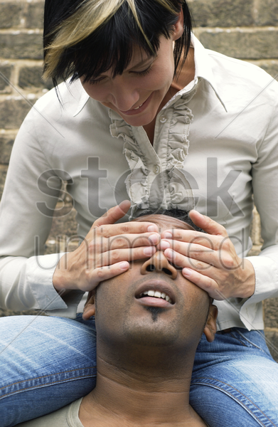 a playful woman closing her boyfriend's eyes stock photo