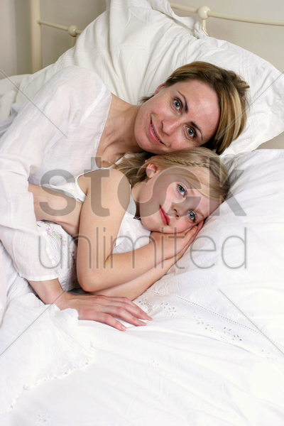 a short hair woman lying on the bed hugging her daughter stock photo