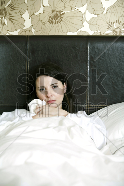 a sick woman in bed stock photo