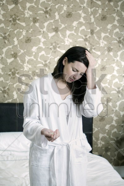 a sick woman with medicine in her hand stock photo