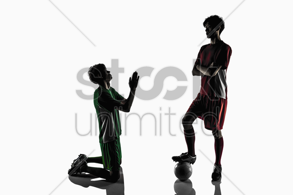 a soccer player begging with opponent stock photo