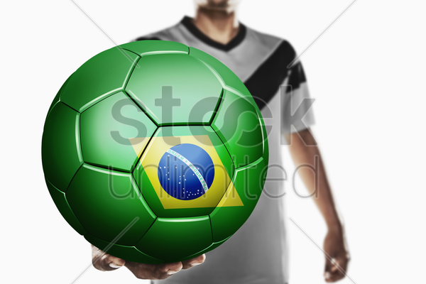 a soccer player holding brazil soccer ball stock photo