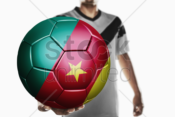 a soccer player holding cameroon soccer ball stock photo