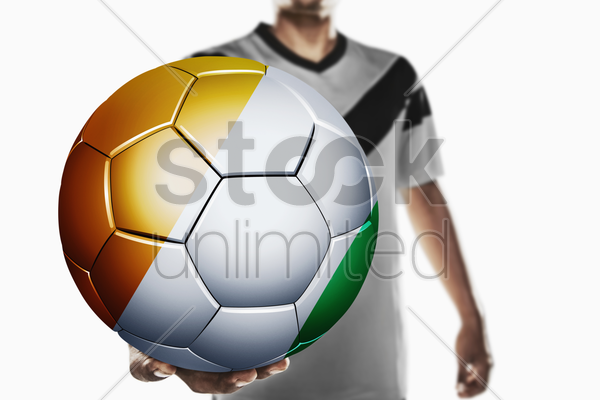 a soccer player holding ivory coast soccer ball stock photo