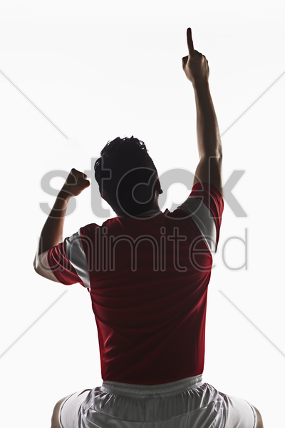a soccer player point his finger to the air stock photo
