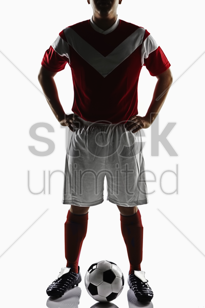 a soccer player posing with a soccer ball stock photo