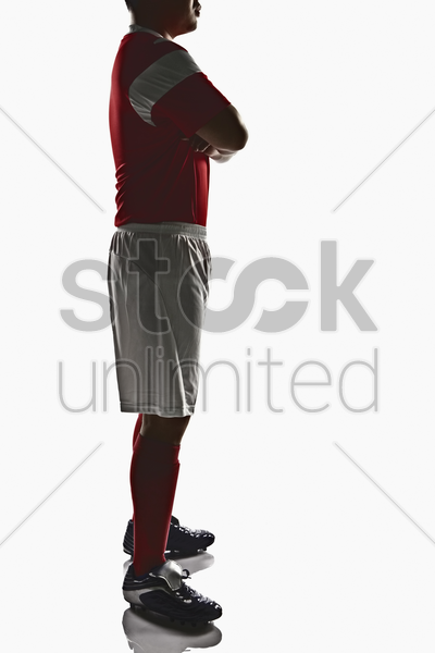 a soccer player with arms crossed stock photo