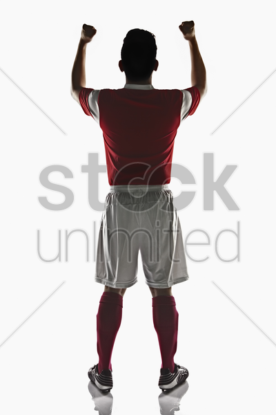 a soccer player with clenched fist in the air stock photo