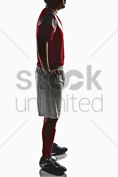 a soccer player with hands on waist stock photo