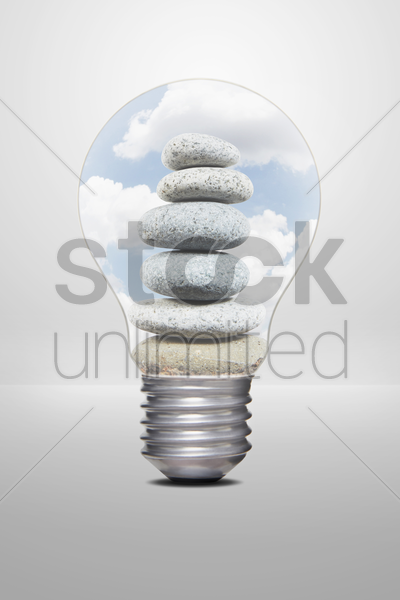 a stack of pebbles placed in a light bulb stock photo