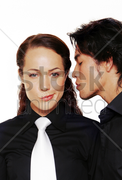a sulking lady in black shirt and white tie being sniffed by her boyfriend stock photo