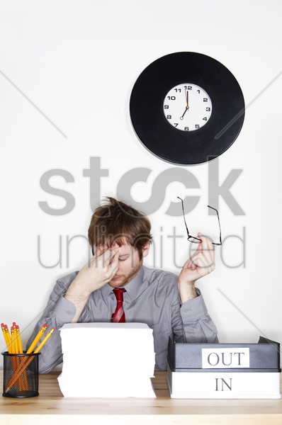 a tired looking man taking out his spectacles while massaging his forehead stock photo