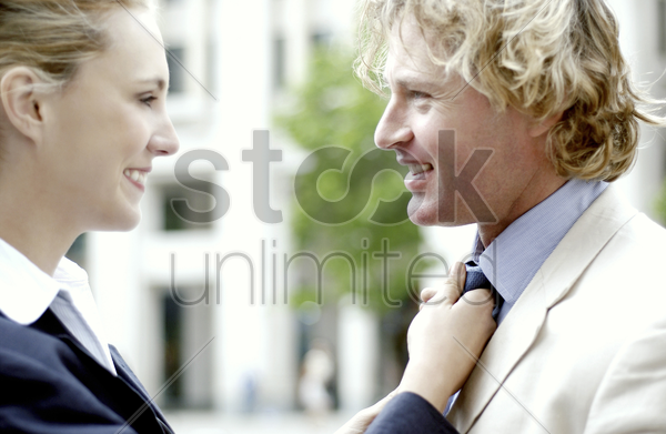 a woman adjusting tie for her boyfriend stock photo