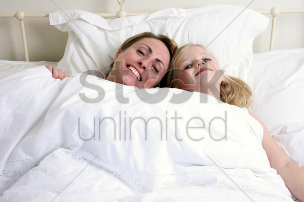 a woman and her daughter lying on the bed together stock photo