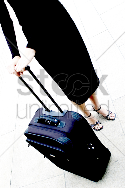 a woman and her travelling suitcase stock photo