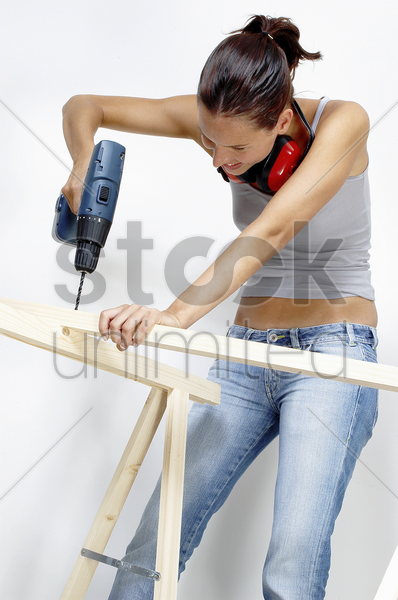 a woman drilling a hole on a wood stock photo