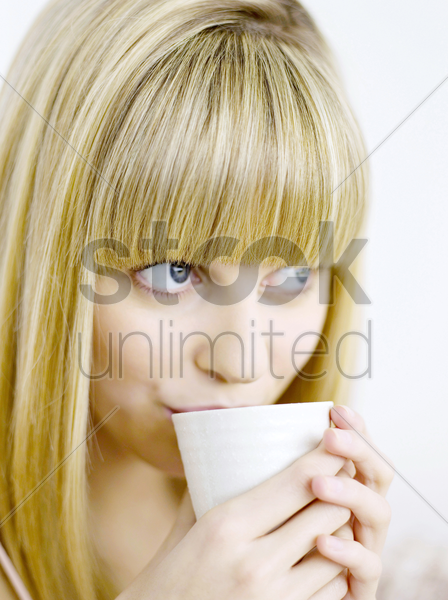 a woman drinking coffee stock photo