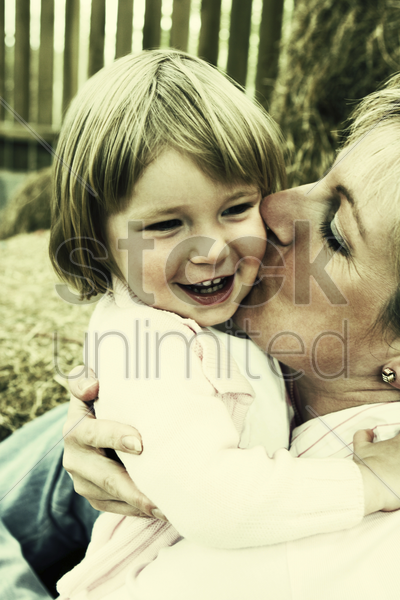 a woman giving her daughter a peck on the cheek stock photo
