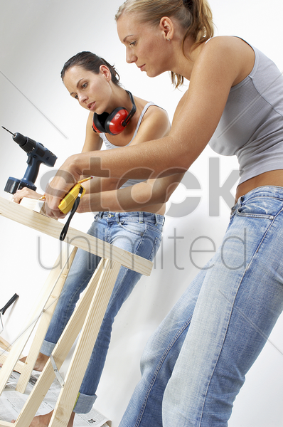 a woman helping her friend to measure a wood stock photo