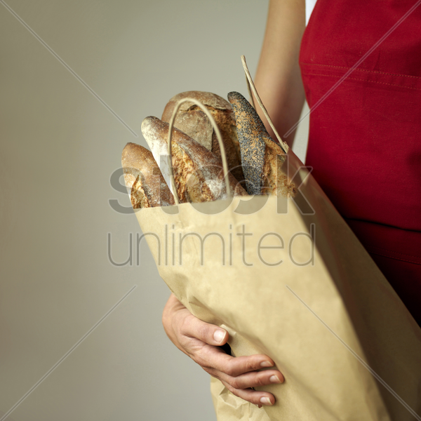 a woman holding a bag of breads stock photo
