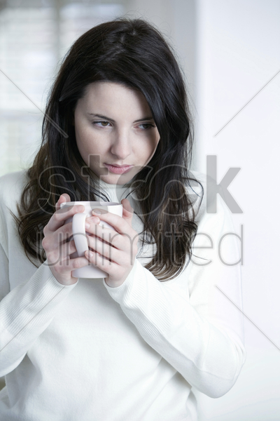 a woman holding a cup of tea stock photo
