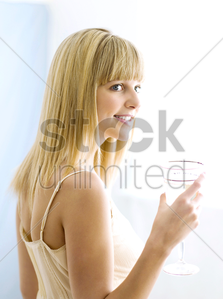 a woman holding a glass of water stock photo