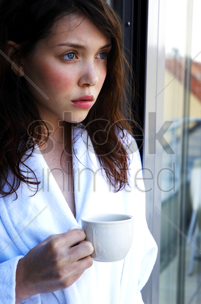 a woman in bathrobe holding a cup while standing by the window stock photo