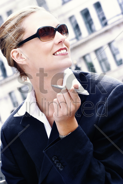 a woman in business suit and sunglasses holding a pen stock photo