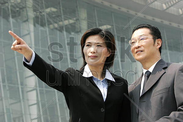 a woman in business suit showing something to a bespectacled man stock photo