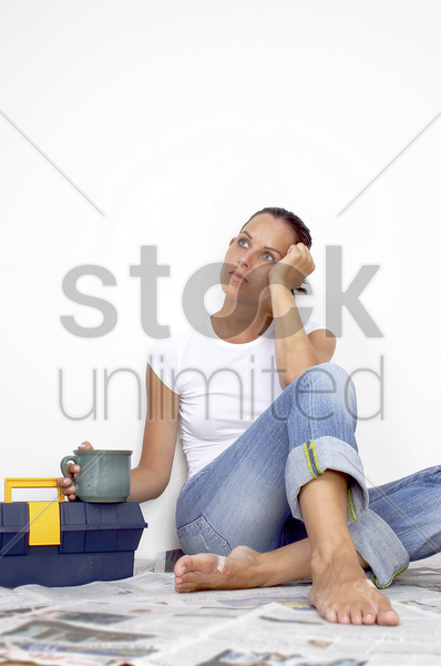 a woman in jeans sitting on a newspaper covered floor stock photo