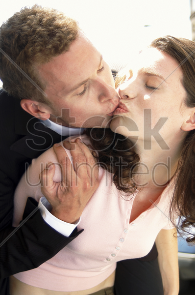 a woman kissing her husband while carrying him on her back stock photo