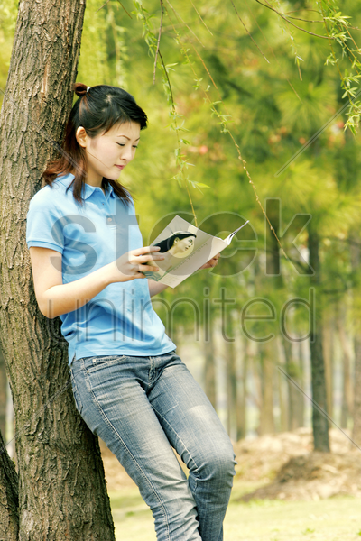 a woman leaning against a tree reading book stock photo