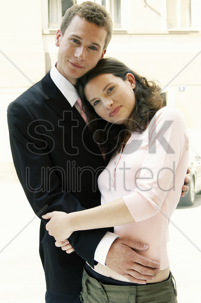 a woman leaning on her husband's chest stock photo